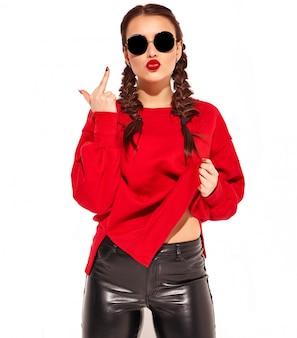 Portrait de jeune modèle femme souriante heureuse avec maquillage lumineux et lèvres colorées avec deux nattes et lunettes de soleil dans des vêtements d'été rouges isolés. montrant baiser signe