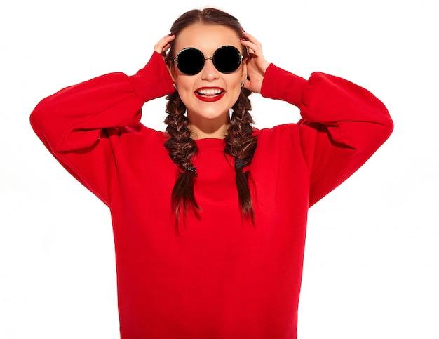 Portrait de jeune modèle femme souriante heureuse avec maquillage lumineux et lèvres colorées avec deux nattes et lunettes de soleil dans des vêtements d'été rouges isolés.