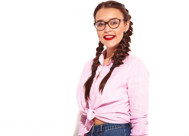 Portrait de jeune modèle de femme souriante heureuse avec maquillage lumineux et lèvres rouges avec deux nattes en été coloré chemise rose attachée isolé