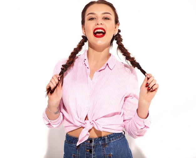 Portrait de jeune modèle femme souriante heureuse avec maquillage lumineux et lèvres rouges avec deux nattes en mains en été coloré chemise rose attachée isolé