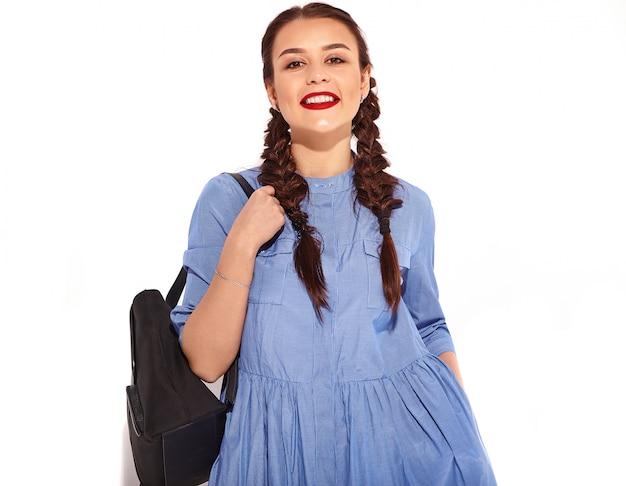 Portrait de jeune modèle femme souriante heureuse avec maquillage lumineux et lèvres rouges avec deux nattes en mains en été robe bleue colorée et sac à dos isolé.