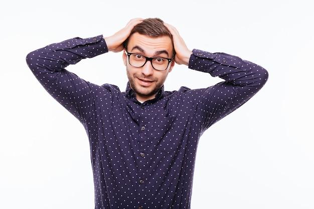 Portrait de jeune modèle masculin barbu déprimé frustré se gratte la tête et serre les dents avec indignation