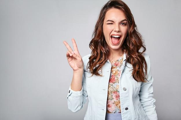 Portrait de jeune modèle riant élégant en vêtements d'été décontractés colorés avec du maquillage naturel sur gris