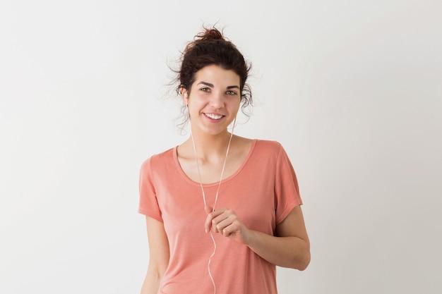 Portrait de jeune naturel à la recherche de sourire heureux hipster jolie femme en chemise rose posant isolé sur fond blanc studio, écouter de la musique dans les écouteurs