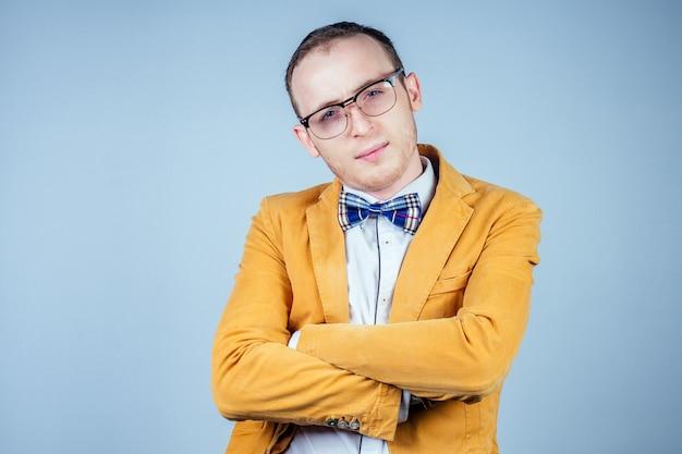 Portrait d'un jeune nerd masculin dans des verres et dans un costume élégant