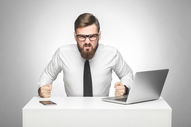 Le portrait d'un jeune patron agressif en colère en chemise blanche et cravate noire est assis au bureau et de mauvaise humeur, frappe la table et serre les dents. intérieur, tourné en studio, isolé, fond gris