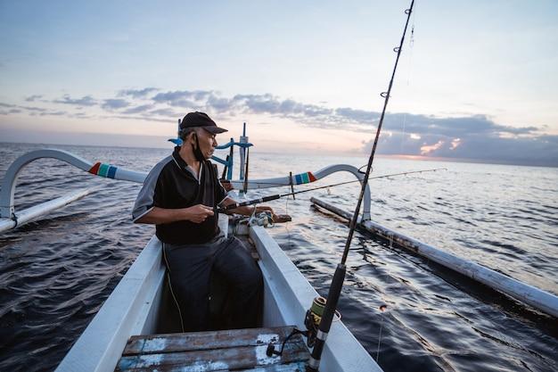 Portrait d'un jeune pêcheur pêchant sur un bateau le matin
