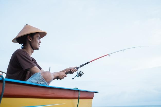 Portrait d'un jeune pêcheur pêchant seul sur un bateau