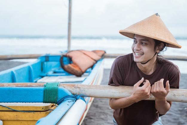 Portrait d'un jeune pêcheur poussant un bateau après la pêche