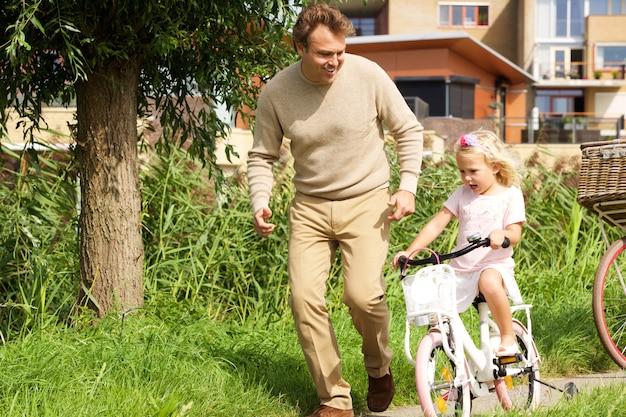 Portrait de jeune père enseignant sa fille à vélo dans le parc