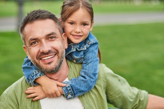 Portrait d'un jeune père joyeux et de sa petite fille mignonne regardant la caméra et s'embrassant tout en