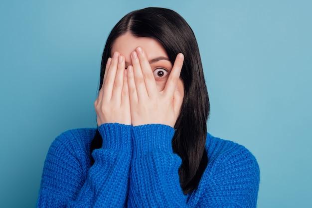 Portrait d'une jeune personne gentille paumes des bras couvrant le visage horreur peur des yeux isolé sur fond de couleur bleu