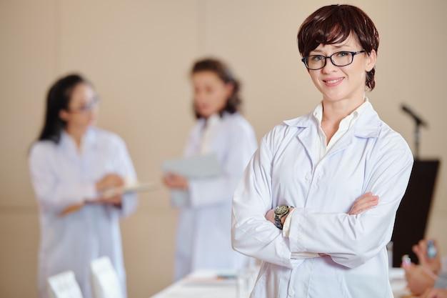 Portrait de jeune pharmacologue confiant à lunettes bras croisés et regardant la caméra