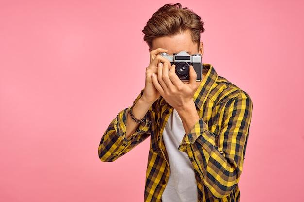Portrait de jeune photographe avec un appareil photo, fond rose