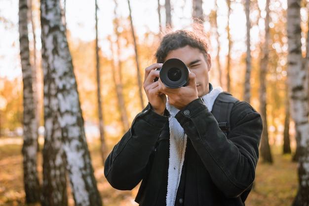 Portrait d'un jeune photographe masculin photographiant des paysages dans la forêt d'automne