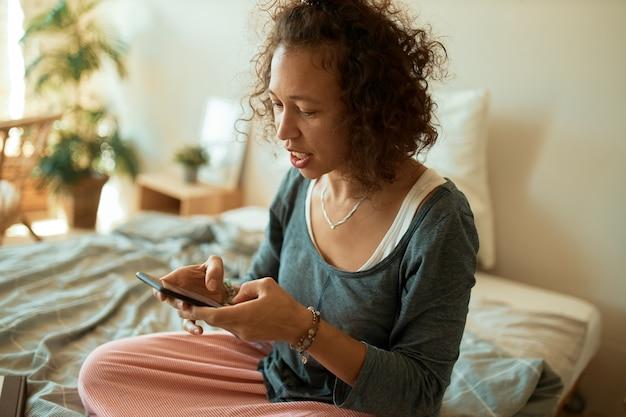 Portrait de jeune pigiste latine habillée avec désinvolture, vendant des marchandises en ligne, assis sur le lit avec un téléphone mobile, en tapant un message texte, en discutant avec le client