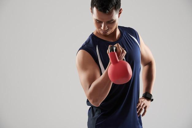 Portrait de jeune powerlifter posant avec poids regardant vers le bas