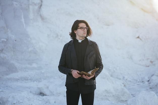 Portrait de jeune prêtre à l'extérieur au coucher du soleil.