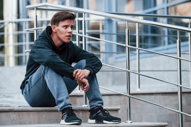 Portrait de jeune principal en vêtements noirs assis dans les escaliers et faisant une pause.