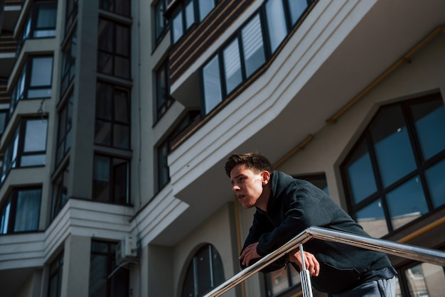 Portrait de jeune principal en vêtements noirs qui s'appuie sur les balustrades et fait une pause.