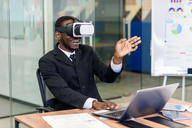 Portrait de jeune professionnel afro-américain à l'aide de la réalité virtuelle augmentée dans un loft moderne. technologie vr