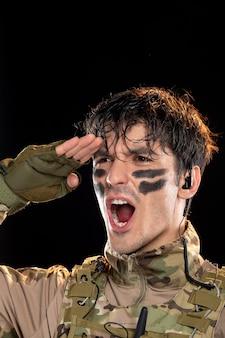 Portrait de jeune soldat en camouflage saluant sur mur noir