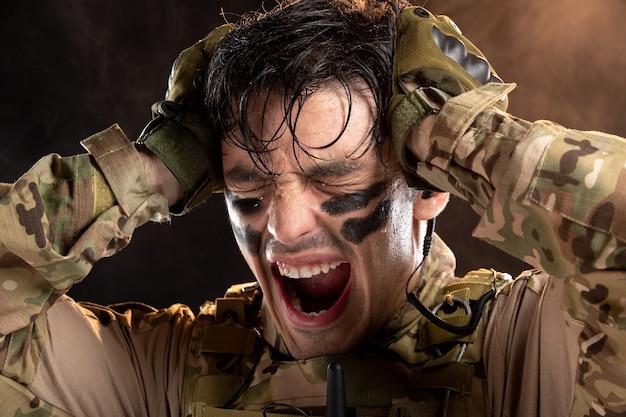 Portrait de jeune soldat en tenue de camouflage hurlant de douleur sur un mur noir