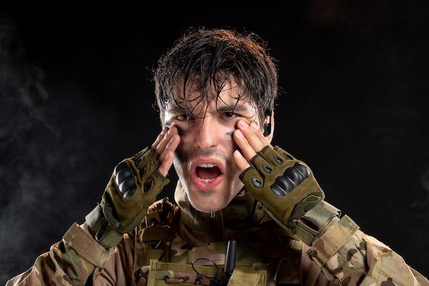 Portrait de jeune soldat en uniforme sur le mur sombre
