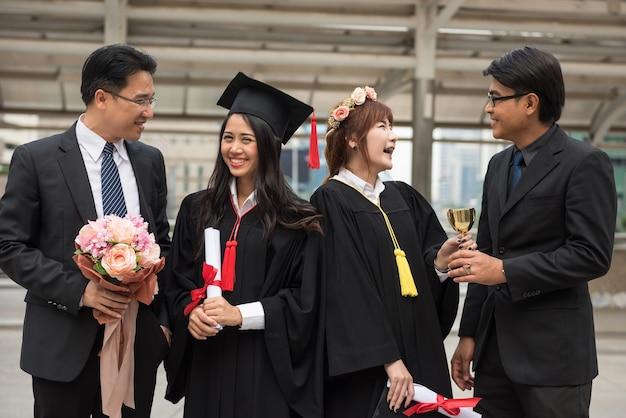 Portrait de jeune sourire étudiantes en robes de graduation noires heureux avec les pères.