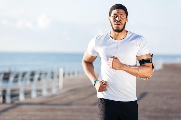 Portrait d'un jeune sportif afro-américain courant sur la jetée le matin