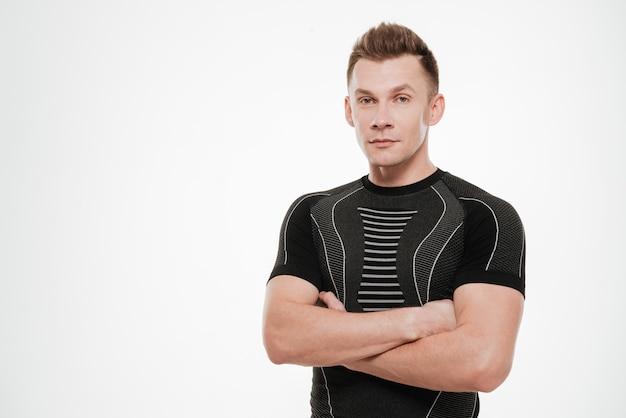 Portrait d'un jeune sportif confiant debout avec les mains jointes