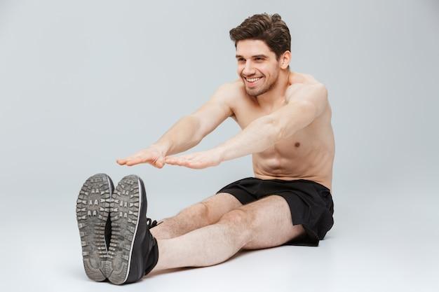 Portrait d'un jeune sportif à moitié nu souriant
