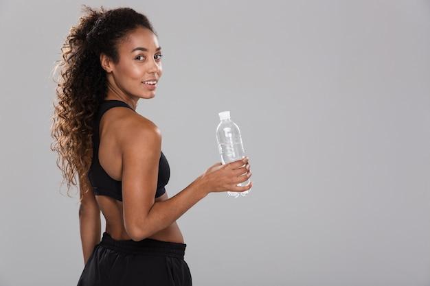 Portrait d'une jeune sportive africaine heureuse au repos après une formation isolée sur un mur gris, tenant une bouteille avec de l'eau