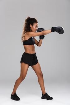 Portrait d'une jeune sportive afro-américaine confiante faisant de la boxe isolée sur fond gris, à l'écart
