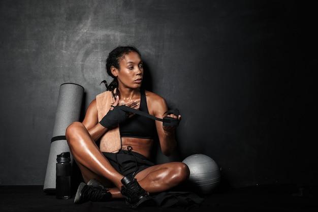 Portrait de jeune sportive afro-américaine portant des enveloppements à la main assis sur le sol avec un équipement de fitness isolé sur fond noir