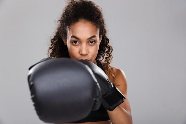 Portrait d'une jeune sportive afro-américaine souriante faisant de la boxe isolée sur fond gris, caméra de poinçonnage