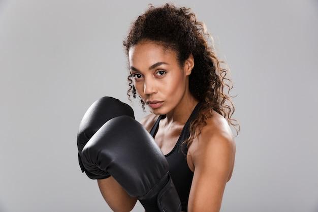 Portrait d'une jeune sportive afro-américaine souriante faisant de la boxe isolée sur fond gris, regardant la caméra