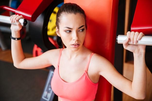 Portrait de jeune sportive séduisante formation des muscles des bras dans la salle de gym