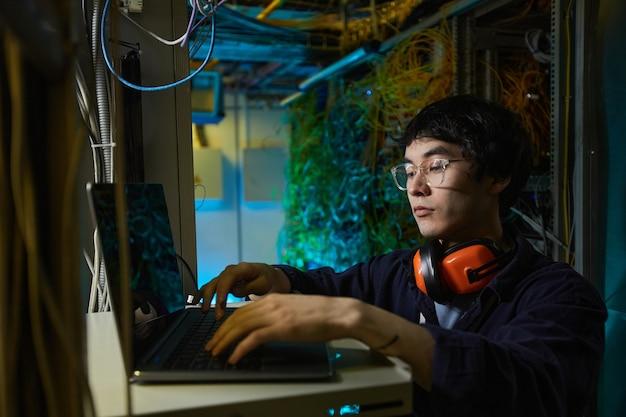 Portrait d'un jeune technicien réseau utilisant un ordinateur portable lors de la configuration de la connexion internet dans la salle des serveurs, espace de copie