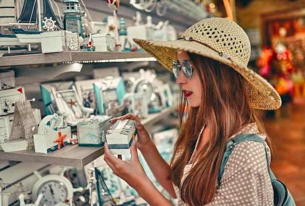 Portrait d'une jeune touriste séduisante vêtue d'un chapeau de paille, d'un chemisier et de lunettes de soleil, qui se promène sur le marché de la ville et sélectionne des boîtes décoratives. le concept de tourisme, de voyage.