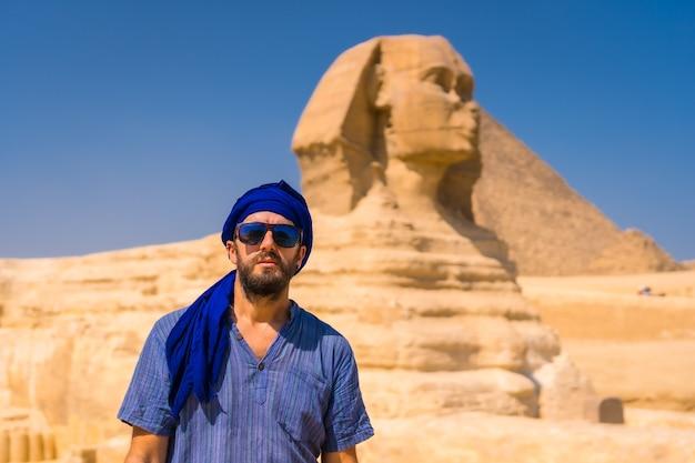 Portrait d'un jeune touriste vêtu de bleu et d'un turban bleu au grand sphinx de gizeh. le caire, egypte