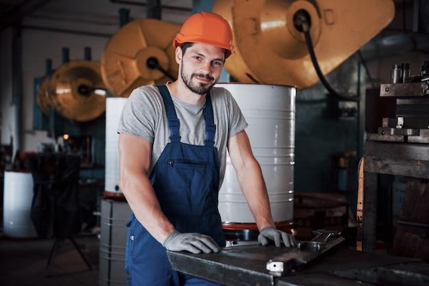 Portrait d'un jeune travailleur dans un casque dans une grande usine de métallurgie.