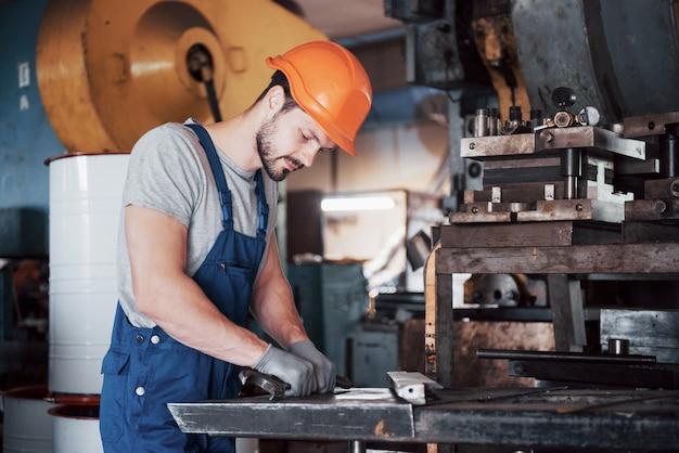 Portrait d'un jeune travailleur dans un casque dans une grande usine de recyclage des déchets.