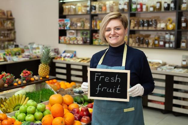 Portrait d'une jeune vendeuse avec un signe dans ses mains fruits frais