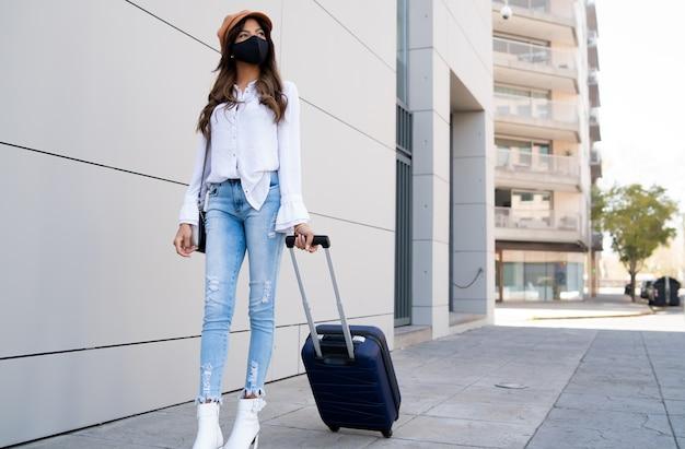 Portrait d'une jeune voyageuse portant un masque de protection et portant une valise en marchant à l'extérieur dans la rue. notion de tourisme. nouveau concept de mode de vie normal.