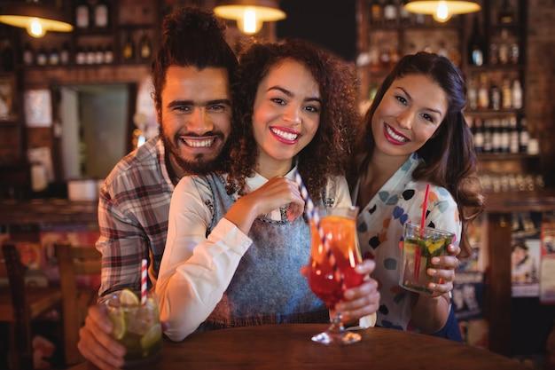 Portrait de jeunes amis ayant des boissons