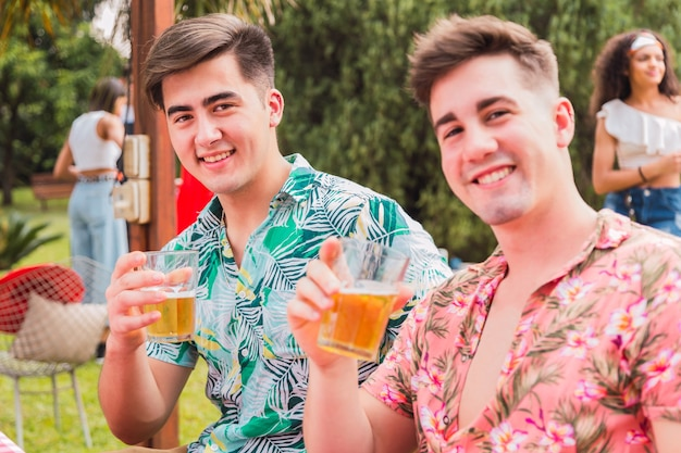 Portrait de jeunes amis buvant de la bière. deux jeunes amis profitent de la journée de pique-nique. concept d'été et d'amitié.
