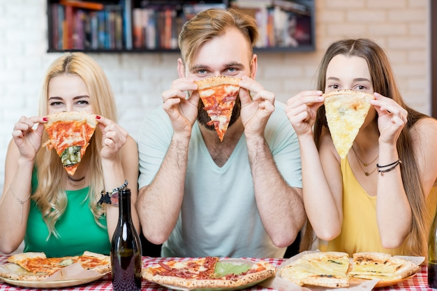 Portrait de jeunes amis drôles vêtus avec désinvolture de t-shirts colorés tenant une tranche de pizza à la maison