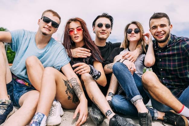 Portrait de jeunes amis élégants assis ensemble