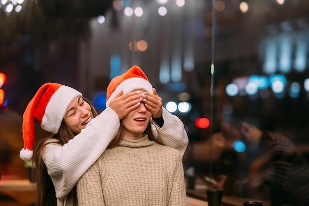 Portrait de jeunes amis mignons heureux étreignant les uns les autres au caffe